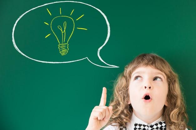 Школьник в классе. счастливый ребенок против зеленой доски. концепция образования Premium Фотографии