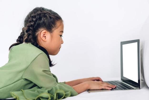Маленькая девочка школьника учится и смотрит на портативный компьютер, делая домашнее задание, изучая знания с помощью системы электронного обучения онлайн.