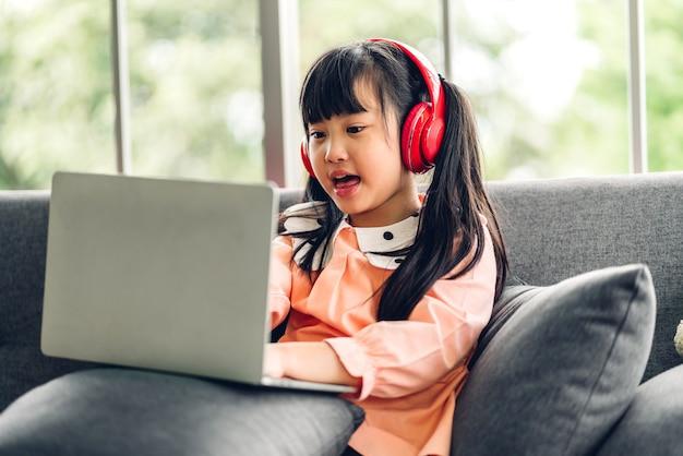 オンライン教育のeラーニングシステムで知識を勉強する宿題を作るラップトップコンピューターを学び、見ている学校の子供少女。