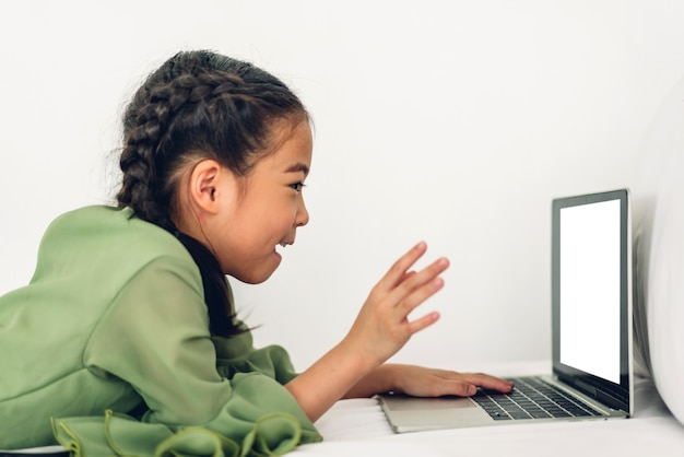 School kid little girl learning and looking at laptop computer making homework studying knowledge with online education e-learning system.