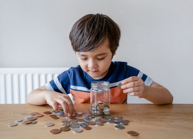 School kid putting money coins into clear jar, child counting his saving money