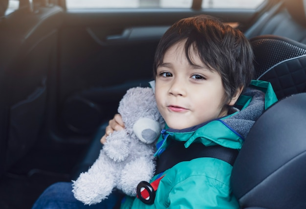 School kid taking his teddy bear traveling with him for explorer on his vocation, child boy sitting in car seat with belt on shoulder