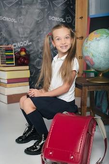 School kid with sitting in uniform girl is back to school