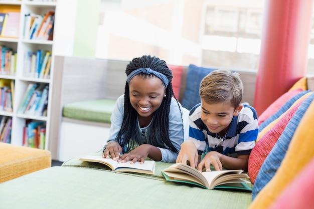 学校の子供たちはソファーに横になって本を読んで