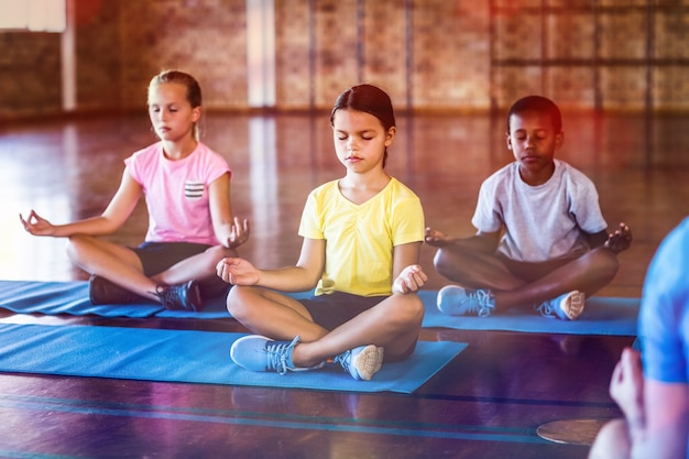 ヨガのクラスで瞑想する学校の子供たち