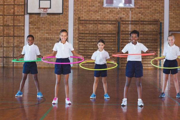 School kids playing with hula hoop in in basketball court
