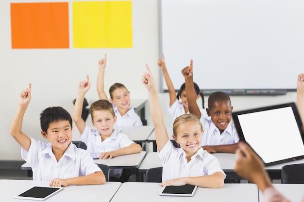 教室で手を上げる学校の子供たち