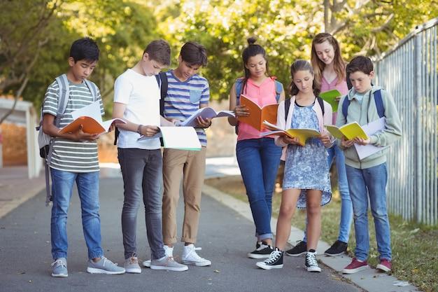 キャンパス内の道路で本を読む学校の子供たち