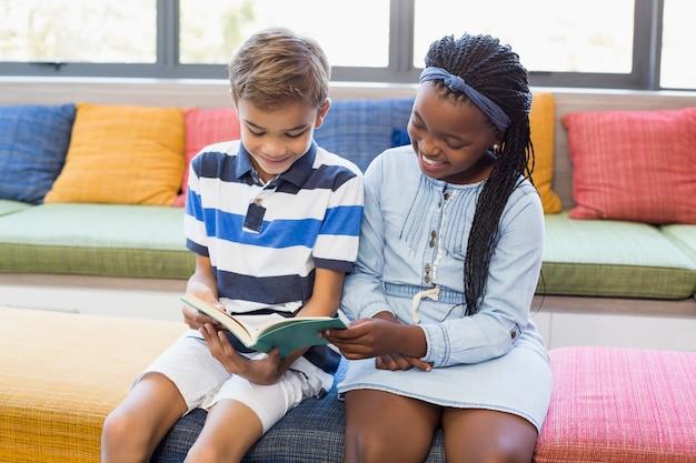 一緒にソファに座って本を読む学校の子供たち