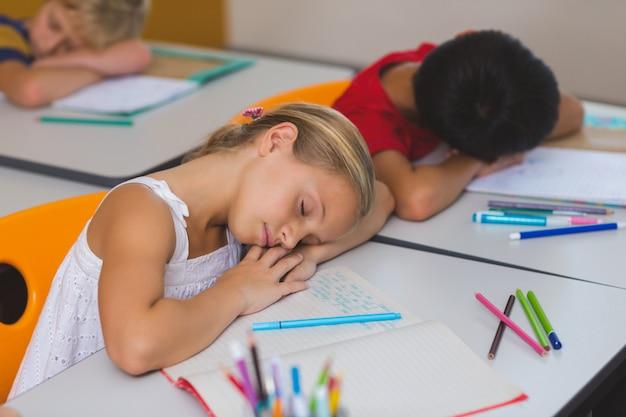 机で寝ている学校の子供たち