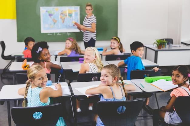 地理の授業中に笑顔の学校の子供たち