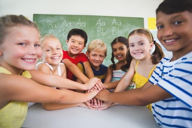 学校の子供たちが教室で手をスタッキング