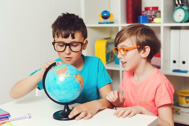 지구본을 공부하는 학교 아이들. 교육 및 지리. 지리를 공부하는 똑똑한 소년들. 함께 숙제를 하는 아이들.
