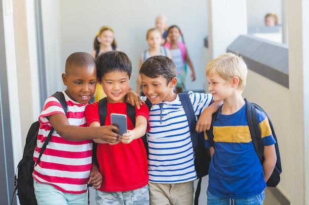 Школьники, делающие селфи на мобильный телефон