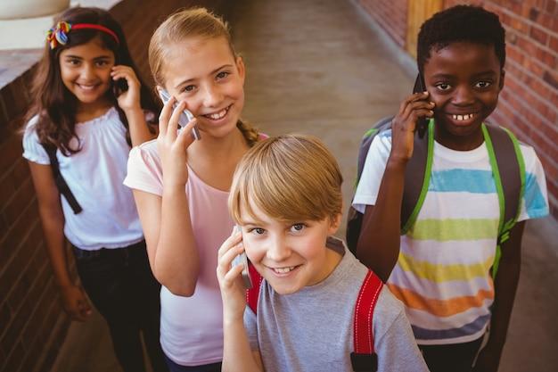 Школьники с помощью мобильных телефонов в школьном коридоре
