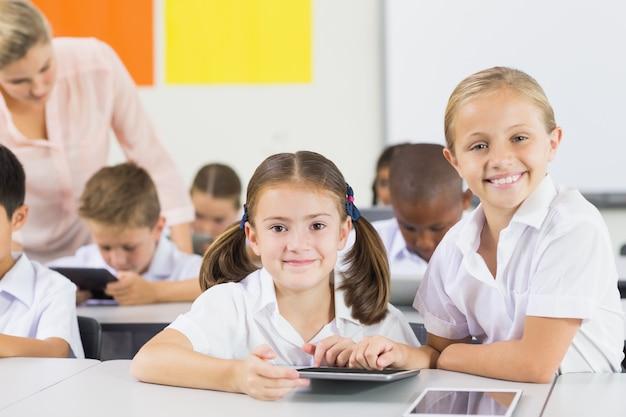 Школьники с помощью цифрового планшета в классе
