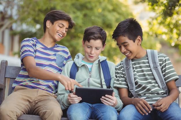 ベンチでデジタルタブレットを使用して学校の子供たち