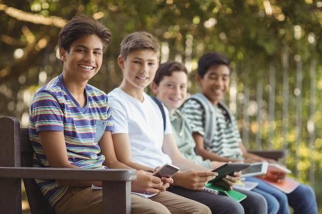 学校のキャンパスのベンチで携帯電話とデジタルタブレットを使用して学校の子供たち