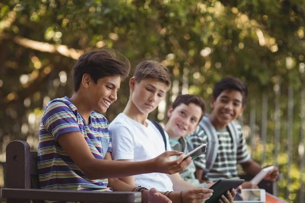 ベンチで携帯電話とデジタルタブレットを使用して学校の子供たち