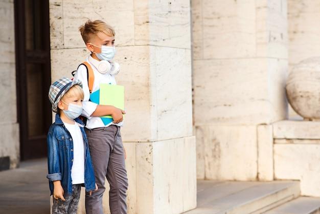 コロナウイルスの発生時にフェイスマスクを着用している学校の子供たち。放課後帰宅する子供たち。コロナウイルスの検疫と封鎖。通りを歩いている医療マスクのかわいい兄弟。