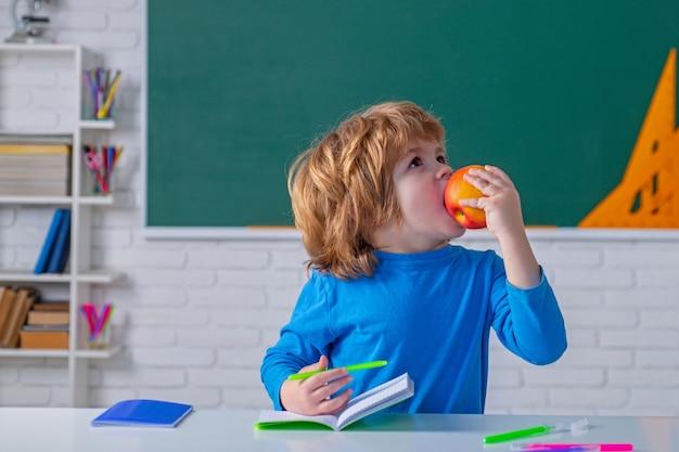 녹색 칠판에 사과가 있는 학교 아이들 초등학교 교육을 공부할 준비가 거의 되지 않았습니다.