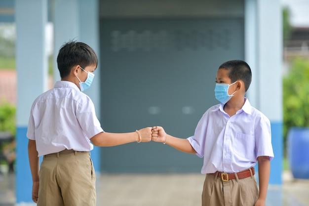 教室でのレッスンでインフルエンザウイルスに対する保護マスクを持つ学校の子供たち