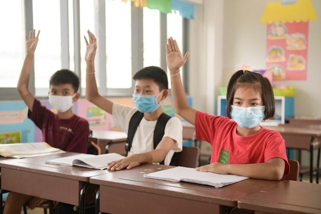 Школьники с защитной маской для лица от вируса гриппа на уроке в классе