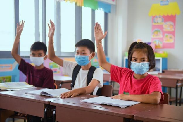 교실 수업에서 독감 바이러스에 대한 보호 얼굴 마스크가있는 학교 아이들