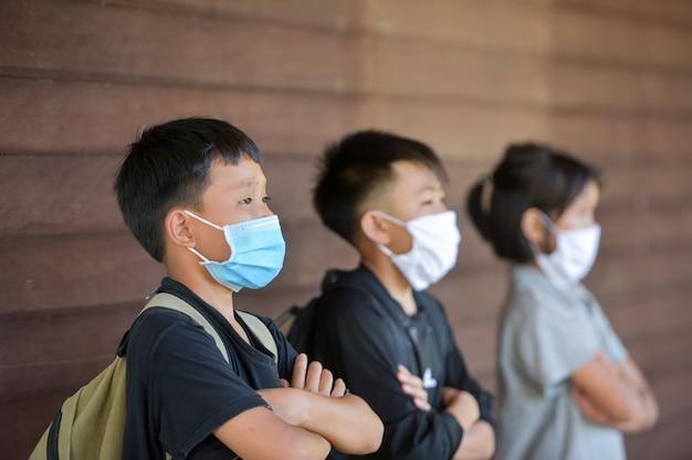 教室での授業でインフルエンザウイルスに対する保護フェイスマスクを持つ学校の子供たち