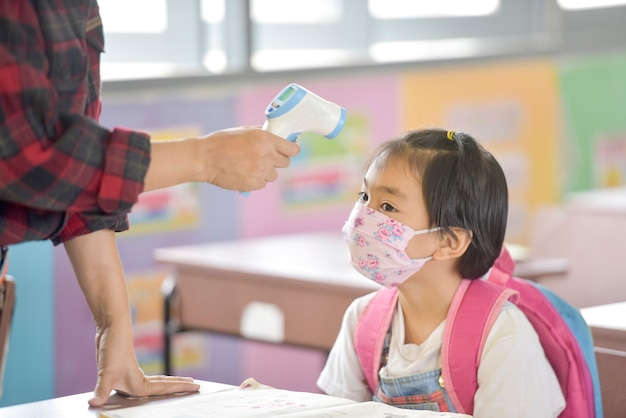 School kids with protection face mask against flu virus at lesson in classroom