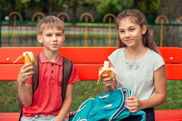 Школьники обедают на открытом воздухе, сидя на скамейке