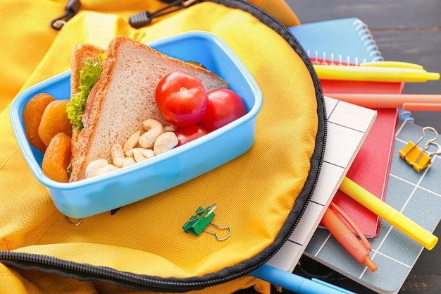 School lunch box and backpack on wooden