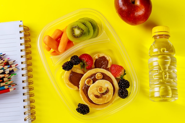 School lunch box for kids with funny face pancakes with fruits and carrot.