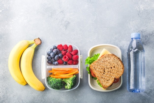 School lunch box with sandwich vegetables berries banana on grey table healthy