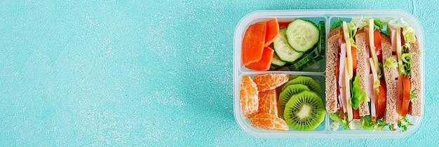 샌드위치, 야채, 물, 과일 테이블에 학교 점심 상자.