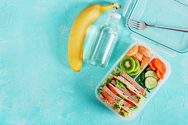 School lunch box with sandwich, vegetables, water, and fruits on table