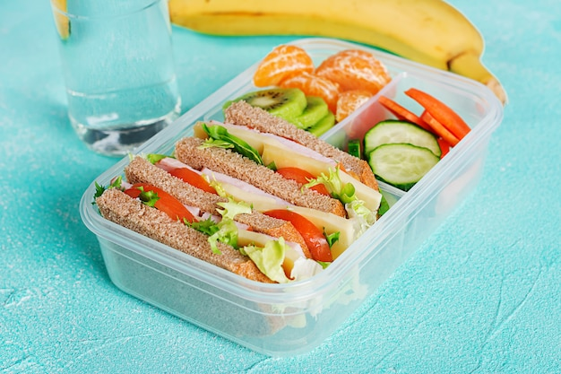 School lunch box with sandwich, vegetables, water, and fruits on table. Free Photo