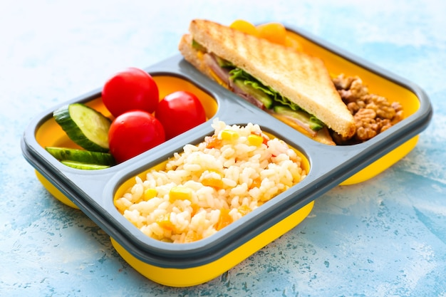 School lunch box with tasty food on color