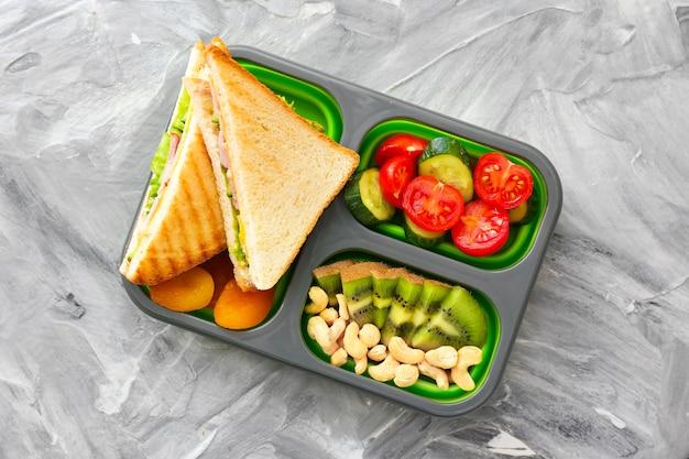 School lunch box with tasty food on grey