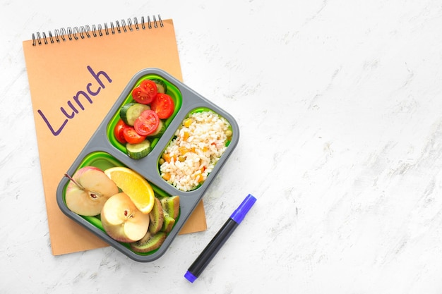 School lunch box with tasty food and notebook on light