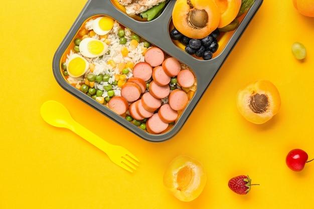 Школьный ланч-бокс с вкусной едой на апельсине