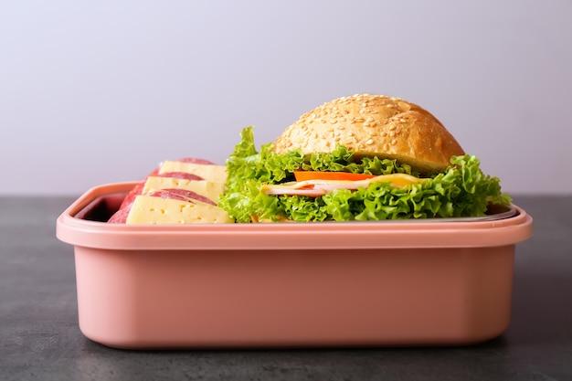 Школьный ланч-бокс с вкусной едой на столе