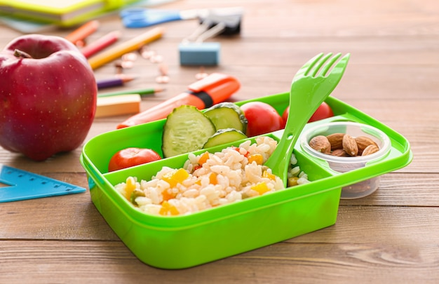 Школьный ланч-бокс с вкусной едой на деревянном фоне