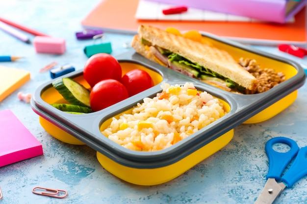 School lunch box with tasty food and stationery on color