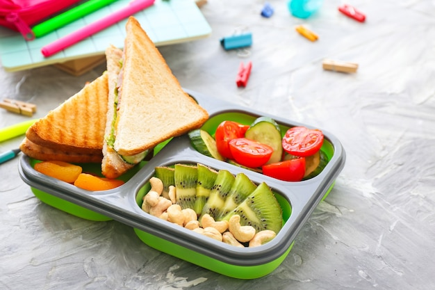 School lunch box with tasty food and stationery on grey