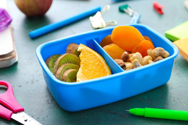 School lunch box with tasty food and stationery on table