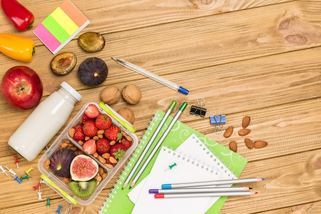 School lunch box with tasty food and stationery