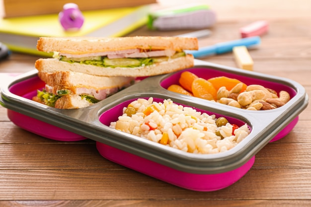 School lunch box with tasty food on wooden background