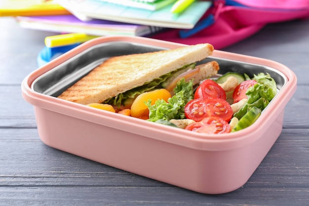 School lunch box with tasty food on wooden