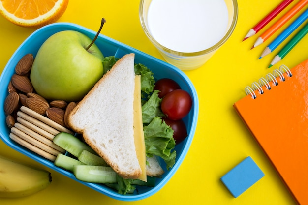 School lunch in the box on the yellow background